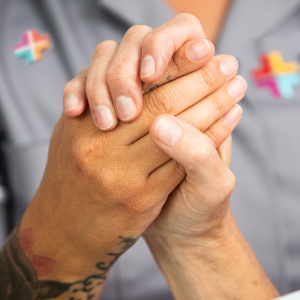 A nurse and a patient at end of life holding each others hand.